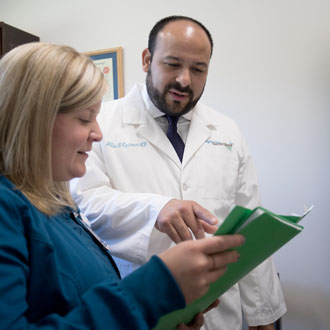 Doctor and nurse reviewing files in a green folder.