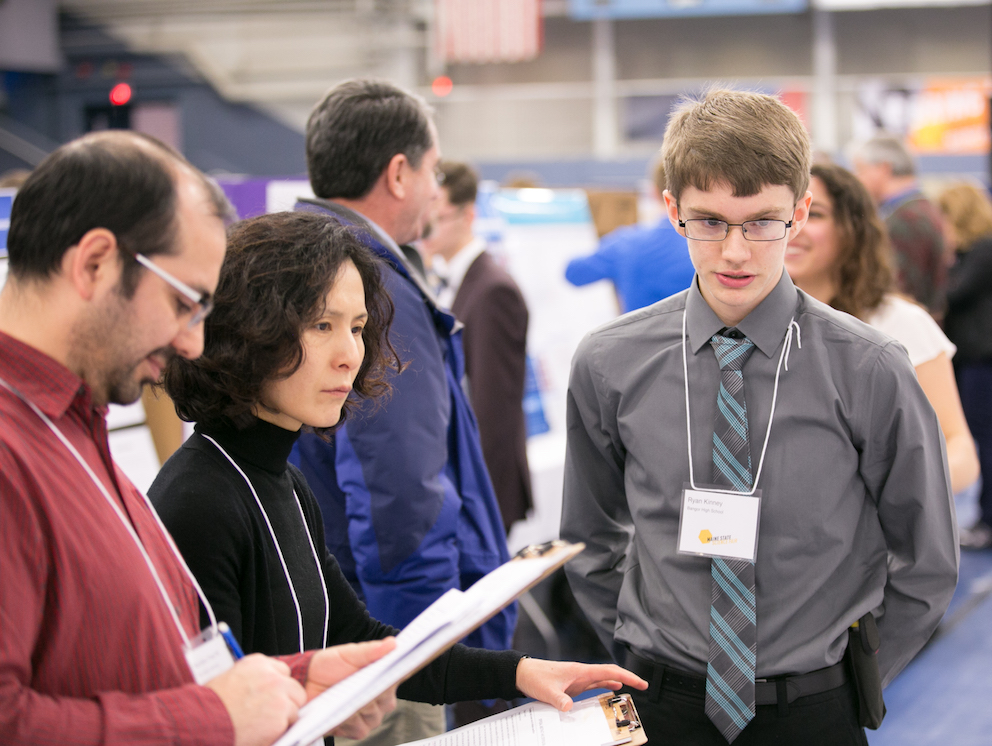 A participant interacting with judges at the Maine State Science Fair