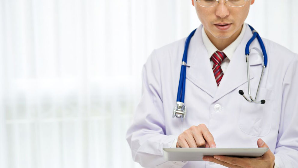 Doctor holding clipboard looking at data.