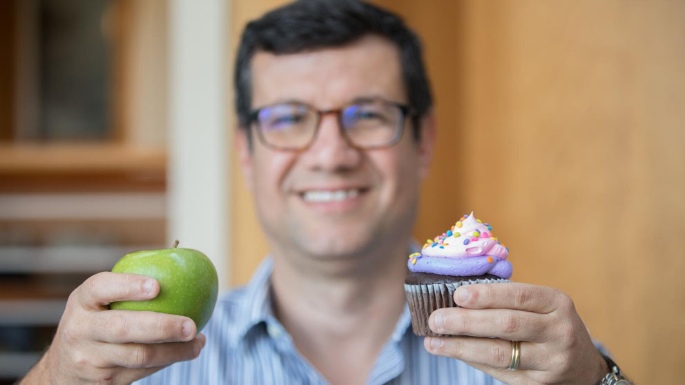Mauro Costa, Ph.D. holding an apple and a cupcake.